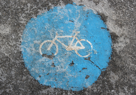 Close view of icy bicycle lane as warning of slippery trail - regulatory blue traffic sign in Italy for route for pedal cycles only