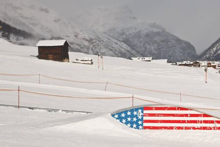 Snowboard ski area with slopestyle flat rainbow box rail painted in the style of american flag, Livigno, Italy Stock Photo