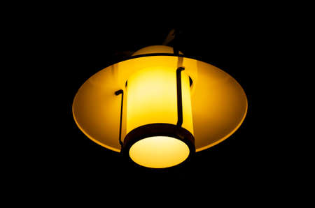 Indoor night lamp isolated against pure black, warm glow