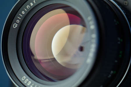 Vintage lens front element close up macro shot with light reflections and visible closed aperture blades 2019