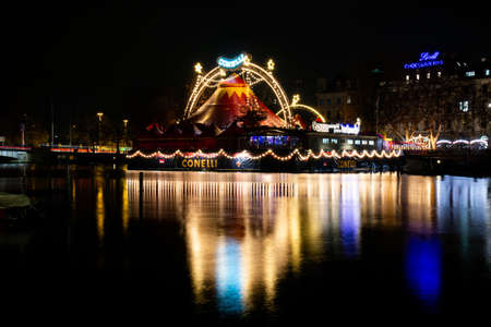 Night time view of a Zurich beer garden floating on the river Limmat, decorative lights and full reflections the water 2019 Фото со стока