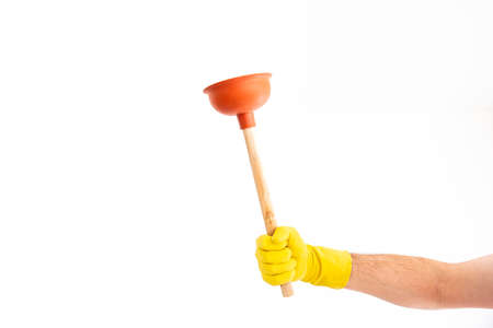 White Caucasian male hand with yellow latex glove holding a sink plunger against white background 2020
