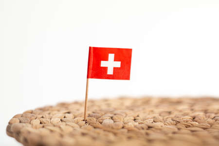 Small Swiss flag on a toothpick pinned on a knitted hemp kitchen pad shallow dept of field white background. 2020