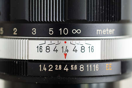 Front view macro shot of a vintage photography fast aperture prime lens with inscribed indented markings on silver aperture ring and black metal barrel 2020