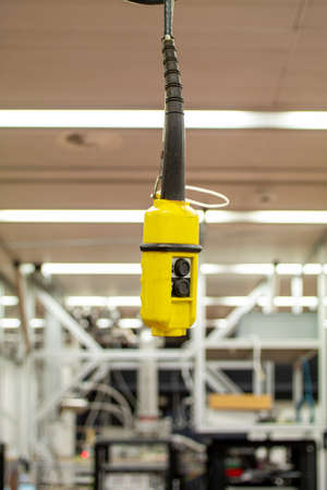 Yellow electric remote crane operating switch module hanging by its wire from the ceiling of a science laboratory 2020 Imagens
