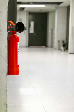 Single red fire extinguisher mounted on a wall inside an empty building corridor shallow dept of field. 2020