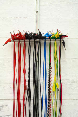 Bunch of vibrant colored electric cables with banana plug connector vertically hanging on a wall 2020