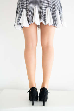 Young Caucasian female legs in stockings, short skirt and black shoes posing isolated against light background 2020 Stock Photo