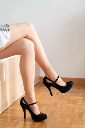 Caucasian woman in sexy stocking short skirt and black shoes standing on the edge of a bed legs crossed natural daylight no face 2020