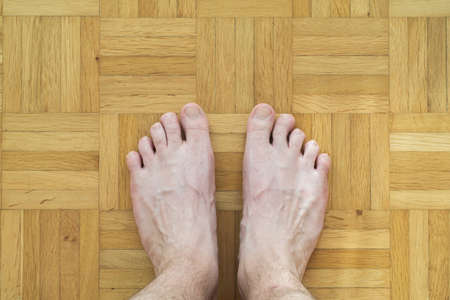 Caucasian male bare feet with crooked toe finger standing on wooden tiles floor top view body hair 2020