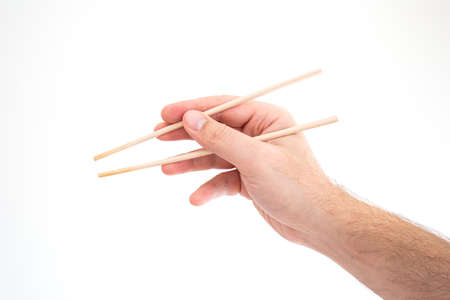 Asian chop sticks held by Caucasian male hand close up shot isolated on white 2020