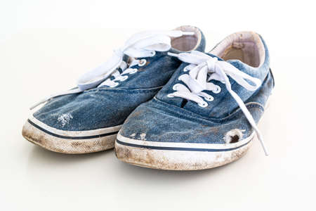 Pair or very badly worn out dirty blue casual leisure shoes with holes in them 2020 Stock Photo