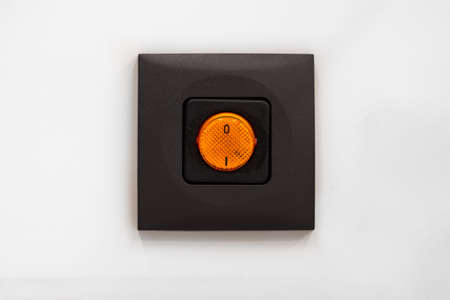 Bright orange electrical switch on brown case close up frontal shot isolated on gray background 2020
