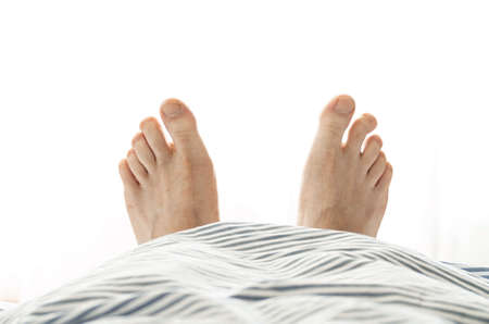 Caucasian male feet with crooked toe poking out of under the bed quilt bright white light in the background 2020