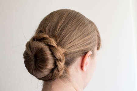 Caucasian young woman with her hair in a french bun with frizzy loose hairs seen from behind not recognizable 2020