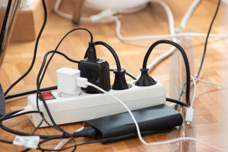 Messy outlet power extension cord on an apartment floor with various charging devices plugged in 2020