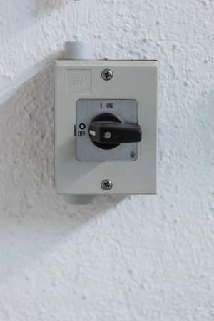 Small square electric switch box with on off markings set on a wall close up shot front view 2020