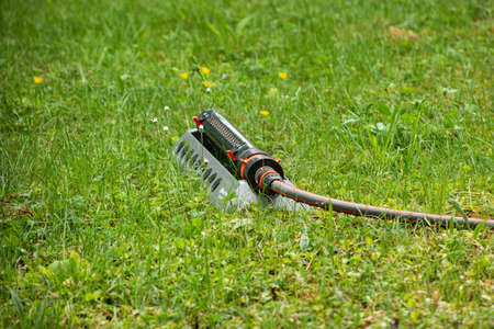 Large garden lawn water sprinkler system with hose set on a green grassy field no operating summer day 2020 Banque d'images