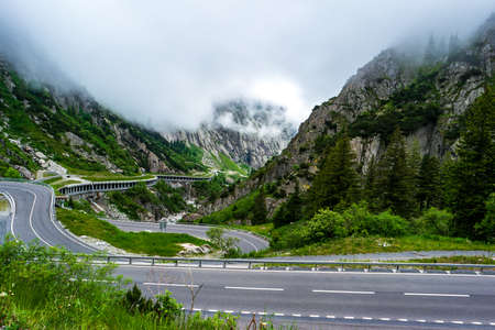High altitude serpentine mountain pass in the Swiss alps Oberalppass top view cloudy summer day 2020