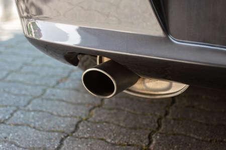 Car engine single exhaust metal tip close up shot next to rear bumper.