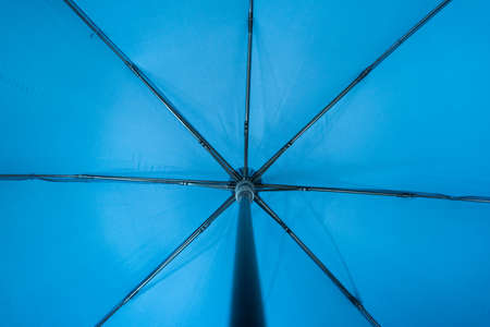 Blue fabric open umbrella mechanism inside point of view concept.