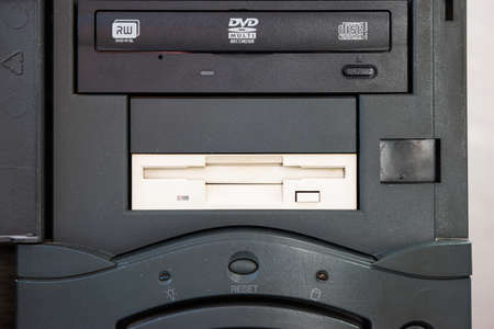 Floppy disk drive and CD DVD write units in a black vertical vintage PC tower close up shot.