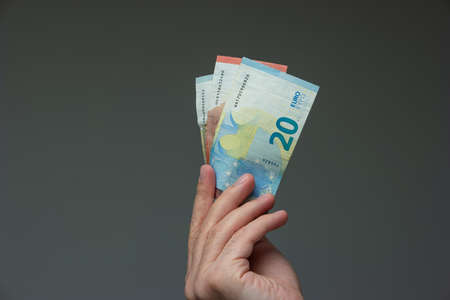 Caucasian male hand holding 3 European Union Euro bills close up shot isolated on gray.