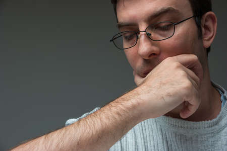 Caucasian male with glasses face in hand sad and worried expression close up shot isolated 30 to 40 years old.