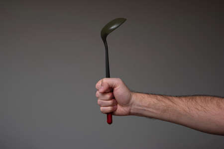 Caucasian male hand grabbing a black plastic ladle with red handle isolated on gray. Banque d'images