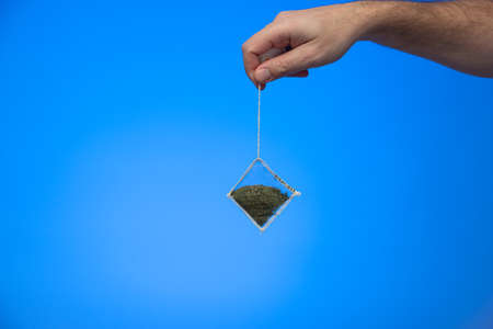 Caucasian male hand holding a tea bag on string isolated on blue background studio shot. Фото со стока