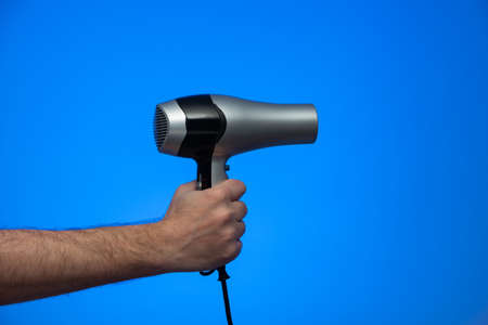 Caucasian male extended arm holding a hair dryer isolated on blue background studio shot. Фото со стока