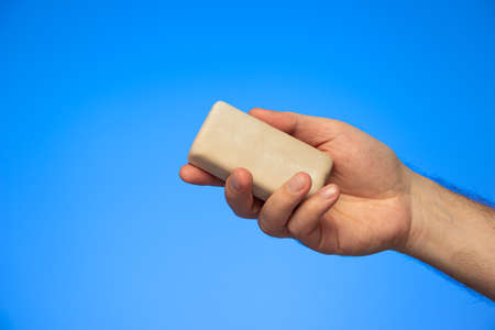 Bar of soap held in hand by Caucasian isolated on blue background studio shot.