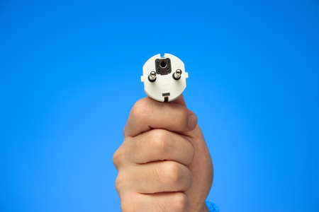 White rubber electrical plug held in hand by Caucasian male hand isolated on blue.