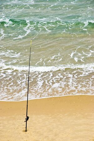 Fishing-rod fixed in the sand.  Expecting for a big catch fish. Stock Photo