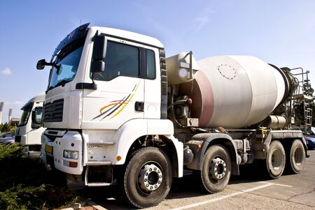 concrete: A truck with concrete mixer. Its used for shipping raw concrete to construction sites.