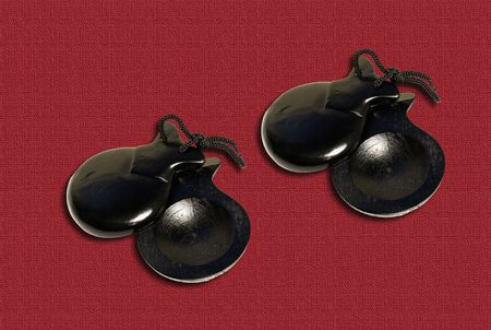 Two pair of castanets on the red textile background.
