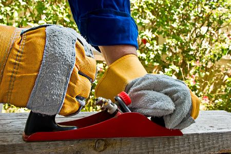 wood cutter: Carpenters hands using a jack-plane