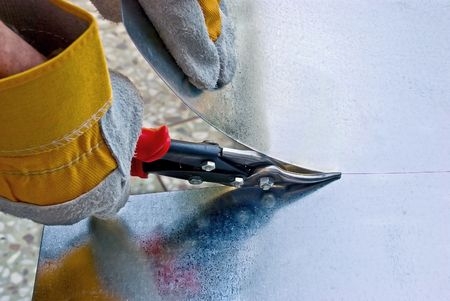 snips: Tinsmith cuts a sheet metal by snips Stock Photo