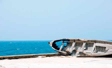 holey: An old wooden holey broken sea boat.