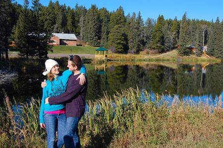 Una joven pareja feliz en la orilla del lago Foto de archivo - 9005542