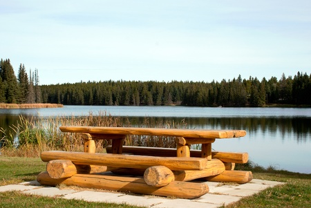 A picnic table with benches on a lake shore photo