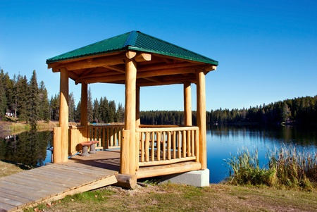 A gazebo located on the shore of a small lake