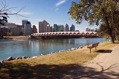 A pedestrian bridge accross  Bow River in Calgary with skyscrapers in the background. photo