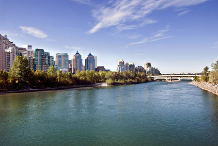 coulorful: A pedestrian bridge accross  Bow River in Calgary with skyscrapers in the background.