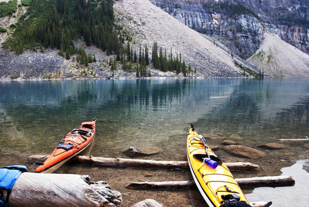 beached: Colorful Kayaks beached on the edge of the Moraine Lake. Stock Photo