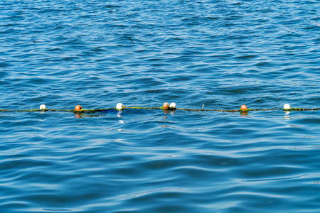 buoy rope barrier on the water with floats Imagens