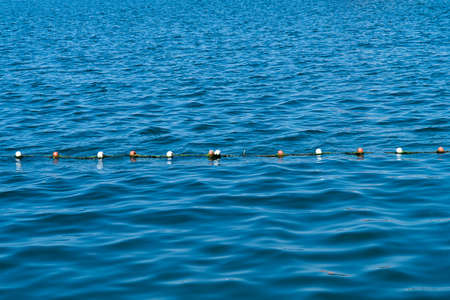 floaters: buoy rope barrier on the water with floats Stock Photo