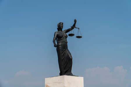 剣と青い曇り空の前で体重計正義の女神像