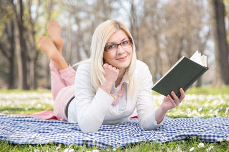 glases: beautiful girl reading book in park Stock Photo
