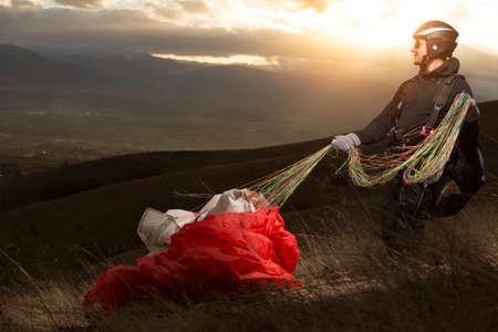 parapente joven hombre en la puesta del sol de la montaña